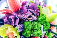 Eheringe auf der bunten Blumenzusammensetzung Stockfotos