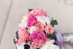 Eheringe auf einem Blumenstrauß von Rosen Lizenzfreie Stockfotos
