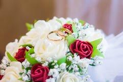 Eheringe auf einem Blumenstrauß von roten Rosen lizenzfreies stockbild