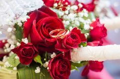 Eheringe auf einem Blumenstrauß von roten Rosen lizenzfreie stockfotos