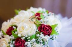Eheringe auf einem Blumenstrauß von roten Rosen lizenzfreies stockfoto