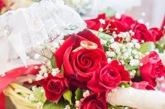 Eheringe auf einem Blumenstrauß von roten Rosen stockbilder