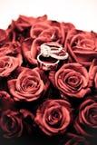 Eheringe auf einem Blumenstrauß von Rosen Lizenzfreies Stockbild