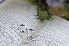 Eheringe auf einem Buch vor der Hochzeit Stockfotos