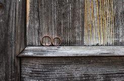 Eheringe auf einem grauen hölzernen Hintergrund Stockbild