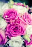 Eheringe auf einem Hintergrund von rosa Rosen Stockfotografie