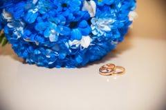 Eheringe auf einem weißen Hintergrund mit einem Blumenstrauß des blauen ribbo Lizenzfreie Stockfotos