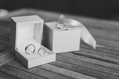 Eheringe auf einer hellen hölzernen Beschaffenheit in einem blauen Kasten Hochzeit J Stockbilder