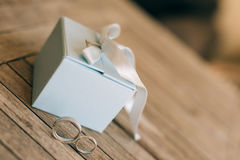 Eheringe auf einer hellen hölzernen Beschaffenheit in einem blauen Kasten Hochzeit J Stockbild
