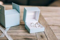 Eheringe auf einer hellen hölzernen Beschaffenheit in einem blauen Kasten Hochzeit J Lizenzfreie Stockfotos