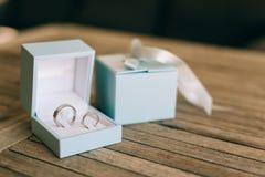 Eheringe auf einer hellen hölzernen Beschaffenheit in einem blauen Kasten Hochzeit J Stockfotografie