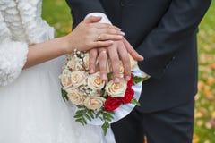 Eheringe auf Händen der Braut und des Bräutigams Stockbild