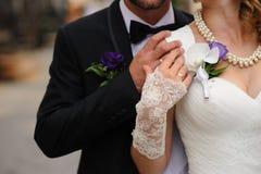 Eheringe auf Händen eines jungen Paares Stockfotografie