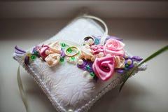 Eheringe auf Kissen mit Blumen, Bänder, Perlen stockfotografie