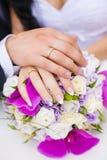Eheringe auf Paar-Händen auf Brautblumenstrauß stockfotos