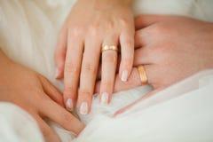 Eheringe auf Paar-Händen, bräutliches weißes Kleid stockbilder