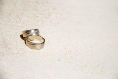 Eheringe auf Sand stockbilder