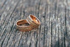 Eheringe in den Händen der Braut auf hölzernem Hintergrund Stockfotografie