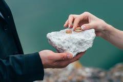 Eheringe in den Händen der Braut auf Steinhintergrund Stockfotos