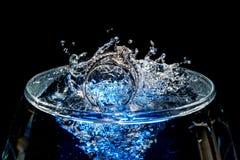 Eheringe, die in ein Tasse Wasser sinken lizenzfreies stockfoto