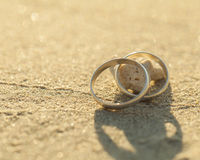 Eheringe gesetzt auf den Strand Stockbild