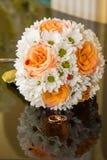 Eheringe liegen auf einem Blumenstrauß von orange Rosen und von weißen Farben lizenzfreie stockfotografie