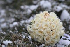 Eheringe mit Blumenstrauß des Winters Stockfotografie