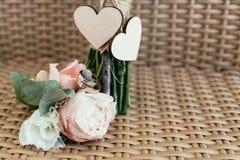 Eheringe mit rosa Rosen gegen zwei hölzerne Herzen Stockfotos