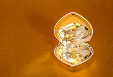 Eheringe mit Schmuckdekorations-Goldhintergrund Stockfotos