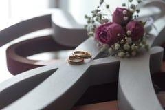 Eheringe nahe dem Fenster, welches auf die Braut mit kleinen Blumen wartet stockbilder