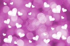 Eheringe umgeben durch lovehearts auf rosa bokeh Hintergrund lizenzfreie abbildung