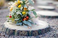 Eheringe und Blumenstrauß auf Stumpf Stockfotos