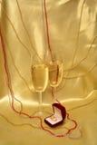Eheringe und Gläser mit Sekt auf einem goldenen Hintergrund lizenzfreie stockfotografie