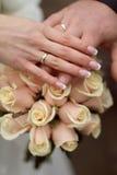 Eheringe und Hände auf Hochzeitsblumenstrauß Stockbild