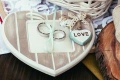Eheringe und Herz mit Liebe unterzeichnen auf Zeremonie Lizenzfreie Stockfotografie