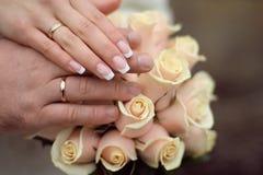 Eheringe und Hände auf Roseblumenstrauß Stockbilder