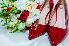 Eheringe und Hochzeitsblumenstrauß auf einem weißen Hintergrund Stockfoto