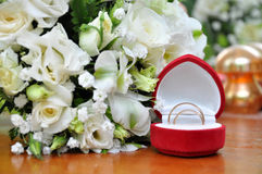 Eheringe und weiße Rosen-Blumenstrauß Stockfoto