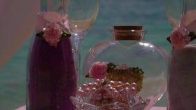Eheringe und Weingläser auf dem Tisch nahe bei dem Meer Detail einer Eleganzfarbbandblume stock footage