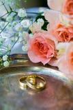 Eheringe vor der Zeremonie, mit verzierten Champagne-Gläsern und Rosen Stockfotografie