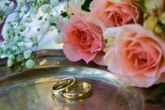 Eheringe vor der Zeremonie, mit verzierten Champagne-Gläsern und Rosen Lizenzfreie Stockfotografie