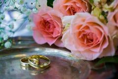 Eheringe vor der Zeremonie, mit verzierten Champagne-Gläsern und Rosen Lizenzfreies Stockfoto
