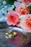 Eheringe vor der Zeremonie, mit verzierten Champagne-Gläsern und Rosen Stockfoto