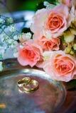 Eheringe vor der Zeremonie, mit verzierten Champagne-Gläsern und Rosen Stockbilder