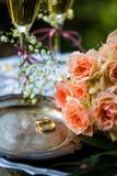 Eheringe vor der Zeremonie, mit verzierten Champagne-Gläsern und Rosen Lizenzfreie Stockfotos