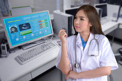 EHR as Electronic health record. Female doctor stand in front of computer while showing electronic health record on monitor Stock Image