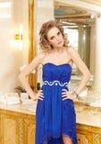 Ehrfürchtige blonde Frau im blauen Kleid Stockfotografie