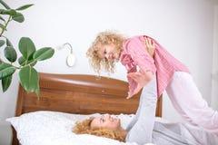 Ehrfürchtige Ingwerfrau, die mit ihrer Tochter spielt lizenzfreies stockfoto