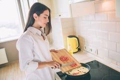 Ehrfürchtige junge Frau kocht Frühstück in der Küche Sie setzt Schnitttomaten in Wanne mit Spiegeleiern und Pilzen Mädchen lizenzfreie stockfotos