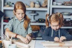 Ehrfürchtige Kinder, die einen rollenden braunen Lehm mit einem Nudelholz auf einer Tabelle bereitstellen lizenzfreies stockfoto